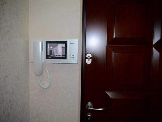 На фото представлен пример установки в квартире традиционного видеодомофона с черно-белым изображением и трубкой