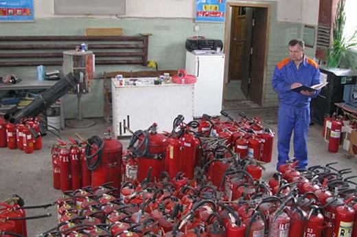 На фото процесс проведения технической диагностики огнетушителей